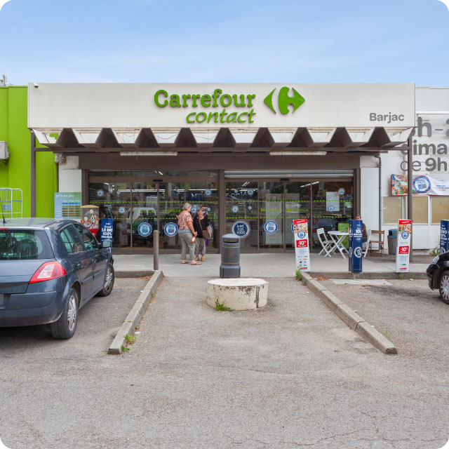 Enseigne Carrefour, Façade du magasin Carrefour Contact à Barjac, parking